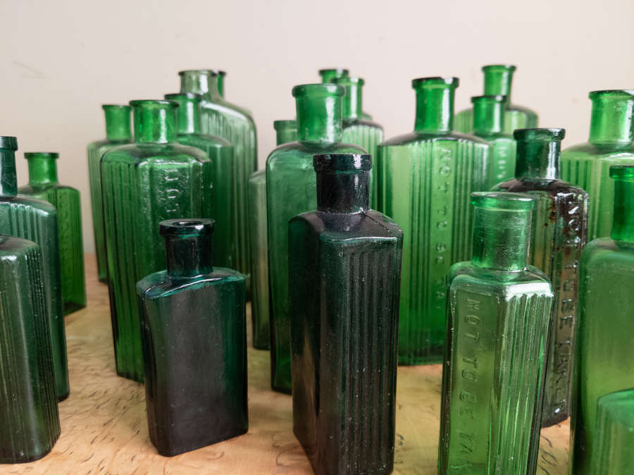 A collection of 30 Green Glass Poison Bottles