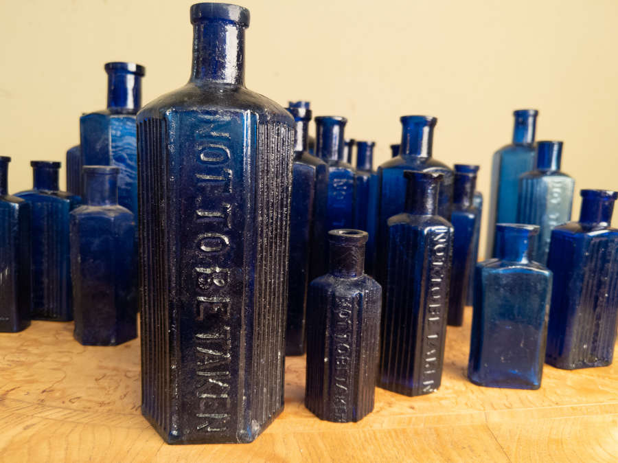 A collection of 30 Blue Glass Poison Bottles